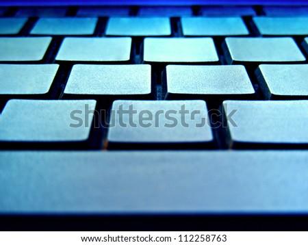 Blank computer keyboard in blue light. Small depth of field. - stock photo
