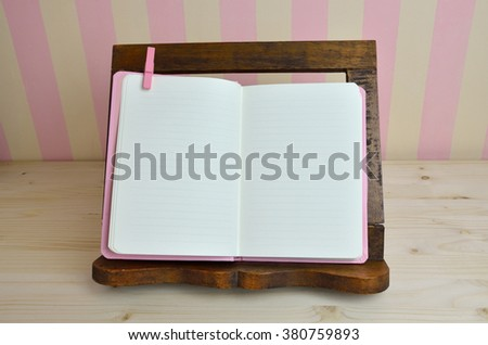 Blank cook book on wooden book holder with pink-yellow kitchen wall - stock photo
