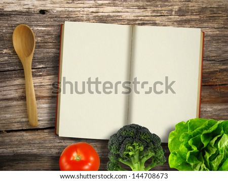 Blank cookbook with scoop and vegetables on wooden table - stock photo