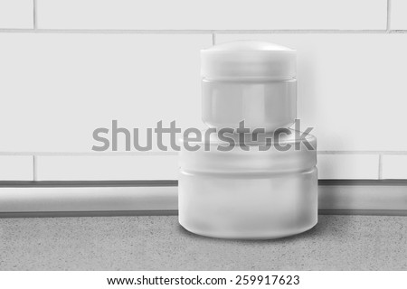 Blank cosmetic jars against white brick wall as a background - stock photo