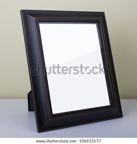 Blank dark wooden picture frame at the desk - stock photo
