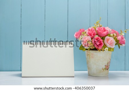 Blank desk calender with pastel rose flowers on white and wooden background - stock photo