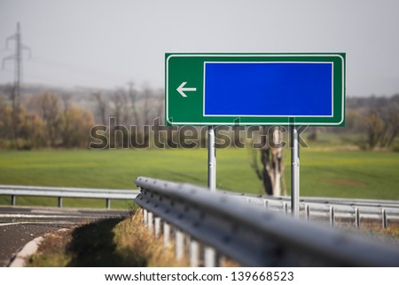 Blank direction sign by the roadside - stock photo