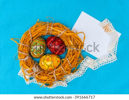 Blank easter card with handmade easter eggs in nest in textile blue background - stock photo