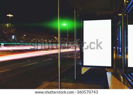 Blank electronic billboard with copy space for your text message or content, public information board on bus stop in the big city at night, advertising mock up with movement of cars on the background - stock photo
