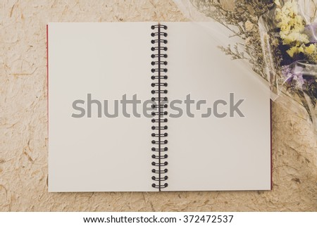 Blank empty notepad and bouquet on mulberry paper background - Vintage filter effect - stock photo