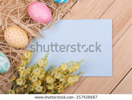 Blank envelope bordered with decorated Easter eggs and flowers - stock photo