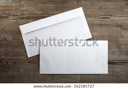Blank envelopes on a dark wooden background. Back and front. Top view. Template for branding identity. - stock photo