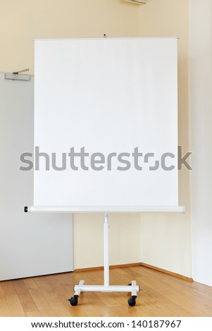 Blank flip chart on hardwood floor in boardroom - stock photo