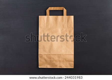 Blank folded paper bag against chalkboard background - stock photo