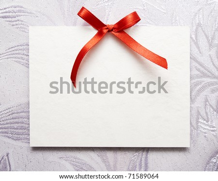 Blank gift tag tied with a bow of red satin ribbon - stock photo