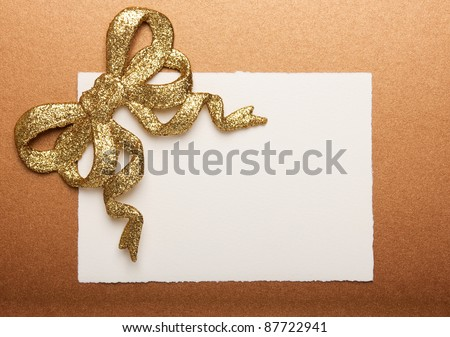 Blank gift tag tied with a gold bow on gold paper - stock photo