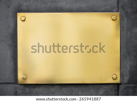 blank gold metal signboard or nameboard on wall - stock photo