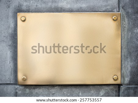 blank gold or brass metal sign or nameboard on concrete wall - stock photo