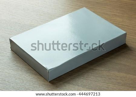 blank gray paper box on dark wood background - stock photo