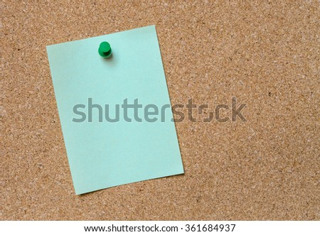 Blank green paper posted on cork board with green tack pin for text and background - stock photo