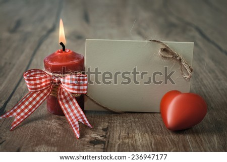 Blank greeting card with burning candle and stuffed checked heart. Happy Valentine! Space for your text - stock photo