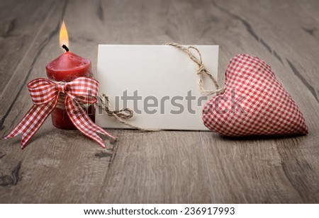 Blank greeting card with burning candle and stuffed checked heart. Space for your text - stock photo