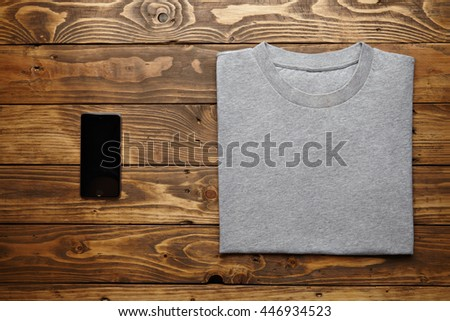 Blank grey t-shirt accurately folded near black smartphone gadget on rustic wooden table top view - stock photo