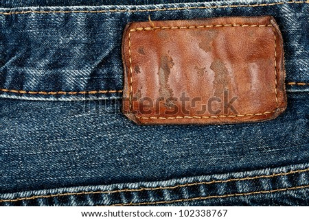 Blank grungy leather jeans label sewed on a blue jeans - stock photo