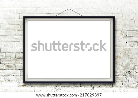 Blank horizontal painting in black frame hanging on white brick wall. Picture proportions match international paper size A. - stock photo