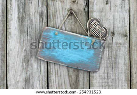 Blank ice teal blue wood sign with country fabric heart hanging on rustic wooden background - stock photo
