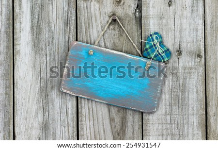 Blank ice teal blue wood sign with fabric heart hanging on rustic wooden background - stock photo