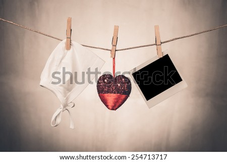 blank instant photo and baby stuff  hanging on the clothesline - stock photo