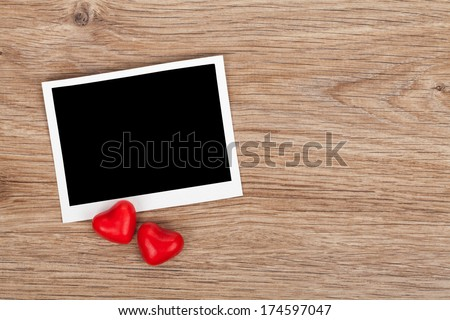 Blank instant photo and red candy hearts on wooden table background - stock photo