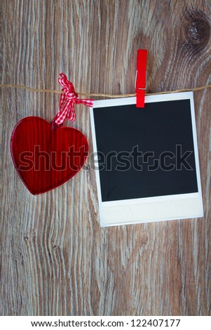 Blank instant photo and  red glass heart hanging on the clothesline, dark grunge background. - stock photo