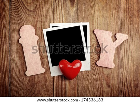 Blank instant photo and red heart on old dark grunge background - stock photo