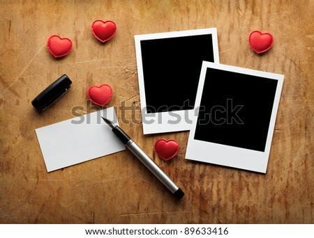 Blank instant photo and small red hearts with blank business (visit) card and fountain pen on old dark grunge background. - stock photo