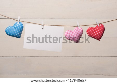 Blank instant photo and small red paper heart hanging on the clothesline. On white wooden background. Love heart hanging on wooden texture background, valentines day card concept - stock photo