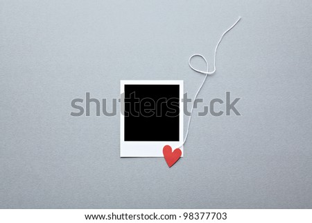 Blank instant photo and small red paper heart with white rope. On dark gray paper background. - stock photo