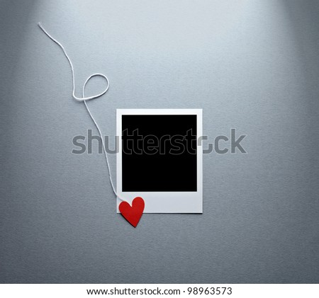 Blank instant photo and small red paper heart with white rope. On textured paper background. - stock photo