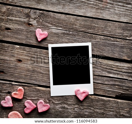 Blank instant photo and sweet red hearts. On old wood background. - stock photo