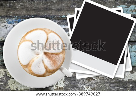 Blank Instant photo frames and cup of coffee on vintage wood table - stock photo