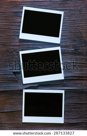 Blank instant photo frames on old wooden background - stock photo