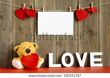 Blank instant photo hanging on rope with lovely hearts, cute teddy bear with the word love on rustic wooden wall. - stock photo