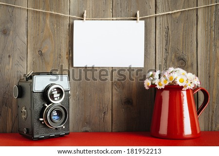 Blank instant photo hanging on rope with retro camera and lovely daisies on red flower pot on rustic wooden wall. - stock photo