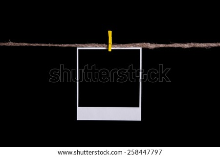 Blank instant photo hanging on the clothesline. Isolated on black background - stock photo