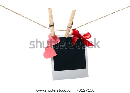 Blank instant photo with red bow and red paper hearts hanging on the clothesline. Isolated on white. - stock photo
