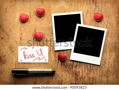 Blank instant photos and small red hearts with blank business (visit) card and fountain pen on old dark grunge background. - stock photo