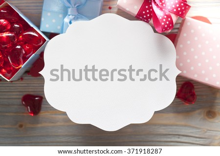 Blank label and gift boxes on wooden background - stock photo