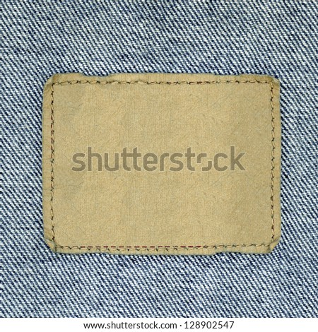 Blank leather jeans label sewed on a blue jeans. Can be used as background for your text. - stock photo