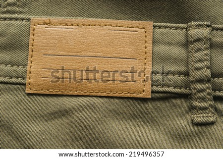 Blank leather label on khaki cloth as a background - stock photo