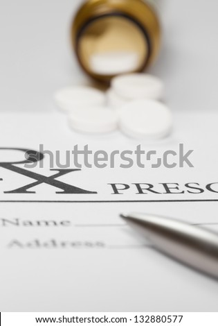 Blank medical prescription with pills on table - stock photo