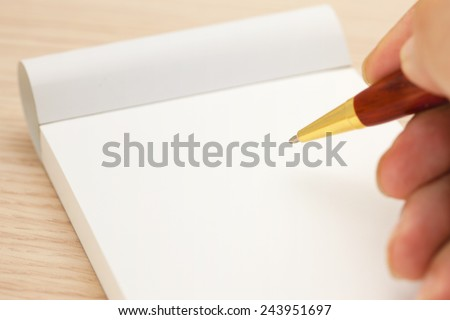 Blank memo pad and a hand holding a pen. - stock photo