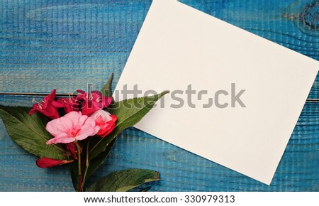 Blank message card and bouquet of flowers on blue wooden rustic table. Love, romantic, concept . Copy space background - stock photo