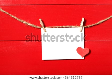 Blank message card with small red heart hanging with clothespins - stock photo